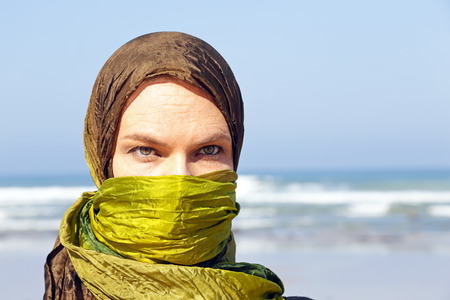 purdah: Beautiful arabic woman with green scarf at the ocean