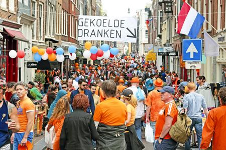 AMSTERDAM - 26 april: Amsterdamse grachten vol met boten en mensen in oranje tijdens de viering van koningen dag op 26 april 2014 in Amsterdam, Nederland