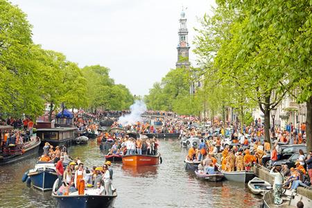 AMSTERDAM - 26 april: Amsterdamse grachten vol met boten en mensen in het oranje op de Prinsengracht tijdens de viering van koningen dag op 26 april 2014 in Amsterdam, Nederland