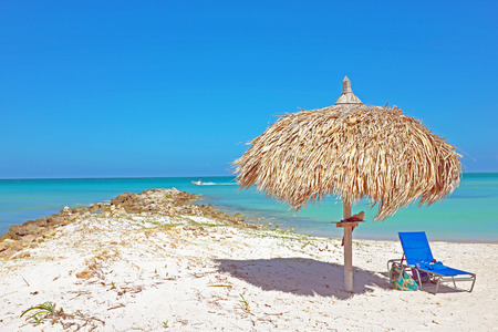 arranging chairs: Grass umbrella at the beach on Aruba in the Caribbean Stock Photo