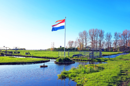 dutch typical: The dutch national flag in a typical dutch landscape Stock Photo