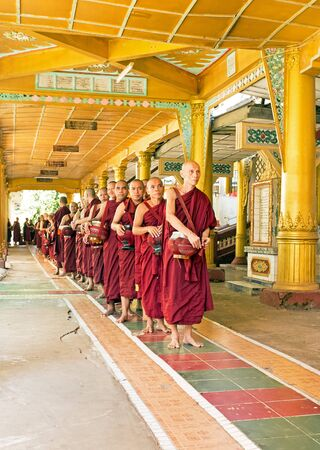 going for it: BAGO, MYANMAR -November 26, 2015: Monks going for lunch in the monastery from Bago in Myanmar in Myanmar.Buddhism is predomi- nantly of the Theravada tradition, practised by 89 of the countrys population. It is the most religious Buddhist country in term