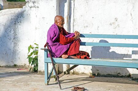 practised: BAGO, MYANMAR - November 24, 2015: Old monk enjoying the sun in the monastery in Bago in Myanmar in Myanmar.Buddhism is predomi- nantly of the Theravada tradition, practised by 89 of the countrys population. It is the most religious Buddhist country in t Editorial