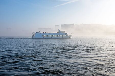 cruiseboat: Cruiseboat in the fog in the harbour from Amsterdam in the Netherlands Stock Photo