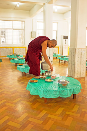 practised: BAGO, MYANMAR -November 26, 2015: Monk serving tea in the monastery from Myanmar.Buddhism in Bago in Myanmar is predomi- nantly of the Theravada tradition, practised by 89 of the countrys population. It is the most religious Buddhist country in terms of