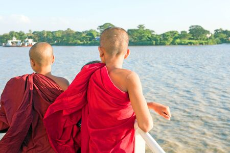 practised: YANGON, MYANMAR - November 24, 2015: Young monks on the ferry at Yangon, Myanmar. Buddhism in Myanmar is predomi- nantly of the Theravada tradition, practised by 89 of the countrys population.