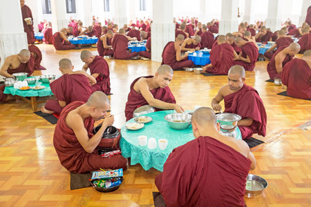 practised: BAGO, MYANMAR -November 26, 2015: Monks having lunch in the monastery at Bago Myanmar. Buddhism in Myanmar is predomi- nantly of the Theravada tradition, practised by 89 of the countrys population
