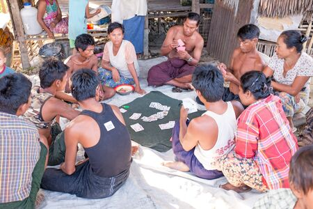 villagers: YANGON, MYANMAR - November 25, 2015: Villagers playing cards in the countryside from Myanmar.