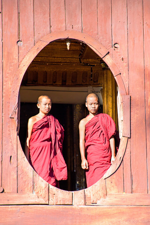 INLE, MYANMAR-NOVEMBER 24: Young novice monks at window wooden Monastery of Shwe Nyan Kgua temple near Inle lake on November 24, 2015 in Inle lake, Shan State, Myanmar Middle of Myanmar.Buddhism is predomi- nantly of the Theravada tradition, by practised
