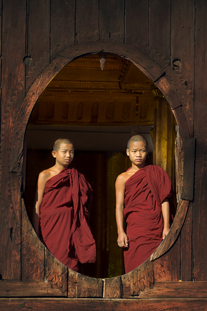 NLE, MYANMAR-April 22: Young novice monks at window wooden Church of Shwe Nyan Kgua temple near Inle lake on April 22.2014 in Inle lake, Shan State, Myanmar Middle of Sajtókép