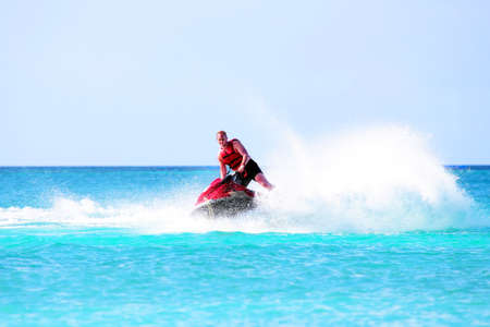 jet skier: Young guy cruising on a jet ski on the caribbean sea Stock Photo