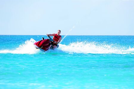 water  skier: Young guy cruising on a jet ski on the caribbean sea Stock Photo