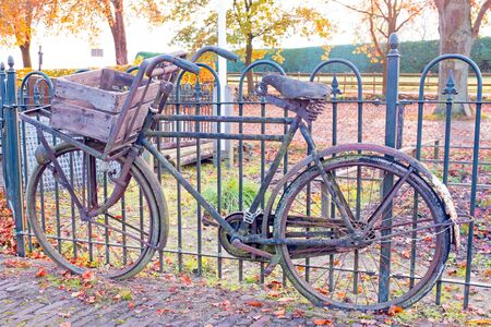 Old fashioned dutch bike against a fence in Netherlands