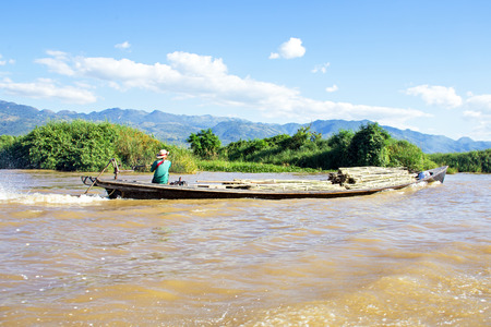 employing: INLE LAKE, MYANMAR - November 23: Transporting bamboo over water. Agriculture in Myanmar is the main industry in the country, accounting for 60 percent of the GDP and employing some 65 percent of the labour force.