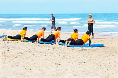 surfers: VALE FIGUEIRAS, PORTUGAL - August 22 2014: Surfers doing excersises on the famous surfers beach Vale Figueiras in Portugal Editorial