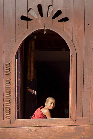 INLE, MYANMAR-November 24: Young novice monk at window wooden Church of Shwe Nyan Kgua temple near Inle lake on November 24.2015 in Inle lake, Shan State, Middle of Myanmar.