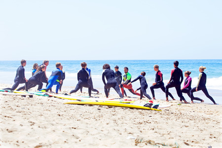 surfers: VALE FIGUEIRAS, PORTUGAL - August 20 2014: Surfers doing excersises on the famous surfers beach Vale Figueiras in Portugal Editorial