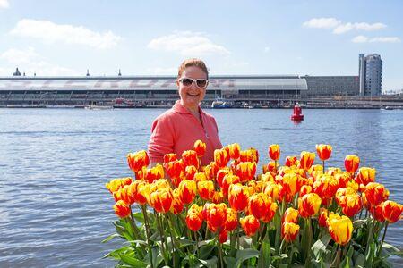 Junge holländische Frau mit orange Tulpen hinter zentralen Station in Amsterdam in den Niederlanden