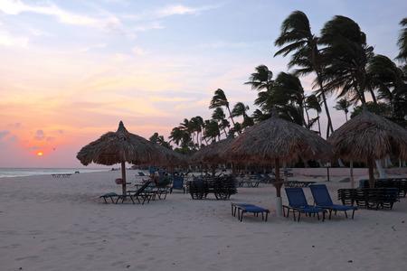 aruba: Beach umbrellas and beach chairs on Manchebo beach on Aruba island at sunset Stock Photo