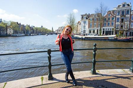 dutch girl: Dutch woman on a medieval bridge in Amsterdam the Netherlands