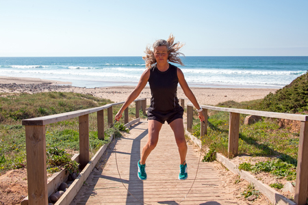 jacks: Mature woman doing jumping jacks with a jumping rope