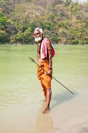 LAXMAN JHULA, INDIA - APRIL 15, 2017: A Hindu sadhu holding a holy trident at the river Ganges in Laxman Jhula on the 15th april 2017 in India