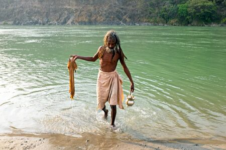 RAM JHULA, INDIA - APRIL 17, 2017: Indian sadhu comes out of the river Ganges after a bath and washing his clothes on 17th of april 2017 in India Editorial