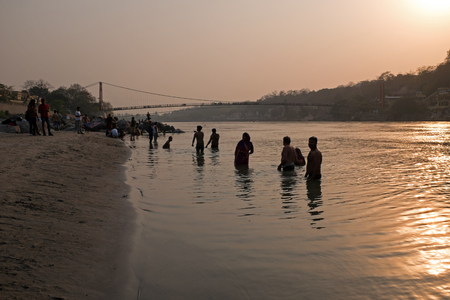 LAXMAN JHULA, INDIA - APRIL 15, 2017: People are taking a bath in the  holy river Ganges in Laksman Jhula on the 15th april 2017 in India Editorial
