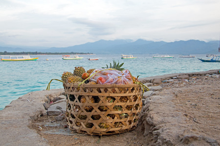 Basket full of ananas and tomatoes in the harbor exported from Gili Meno Indonesia Asia