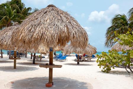 aruba: Beach umbrella and beach chairs on Palm Beach at Aruba island in the Caribbean Sea Stock Photo