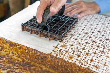 Afdrukken op de stof om batik te maken. Batik maakt deel uit van de Indonesische cultuur.