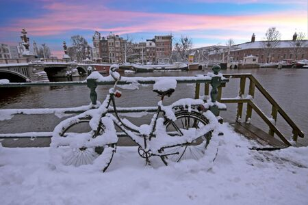 Snowy bicycle in Amsterdam city center the Netherlands at sunset