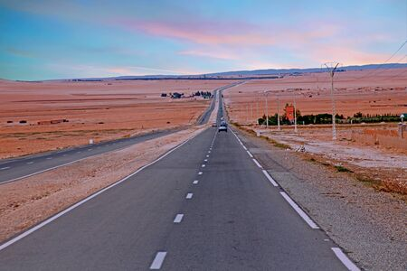 Driving through the Sahara Desert in Morocco Africa at sunset Stock Photo