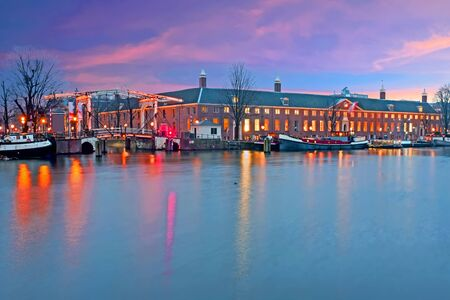 City scenic at the river Amstel in Amsterdam at sunset