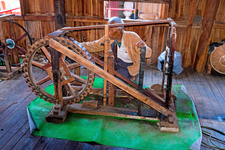 INLE LAKE, MYANMAR - NOVEMBER 22, 2015: Man behind an old fashioned loom in Burma Asia