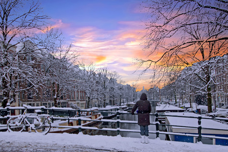 Amsterdam covered with snow  in winter in the Netherlands at sunset Stockfoto