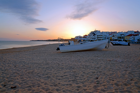 Traditional fisherman boat on the beach in Armacao de Pera at sunset Standard-Bild - 123552688