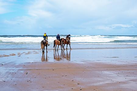 Horse riding at Carapateira beach in the Algarve Portugal Standard-Bild - 123552773