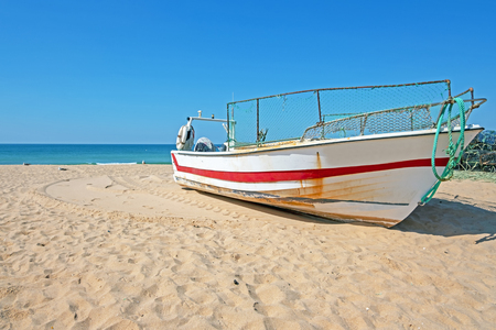 Old fishers boat on the beach in Armacao de Pera in the Algarve Portugal