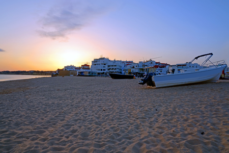 Traditional fisherman boat on the beach in Armacao de Pera at sunset Standard-Bild - 123552788