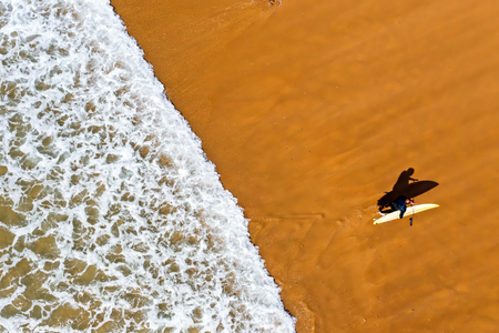 Aerial shot from a surfer coming out of the water from the atlantic ocean Standard-Bild - 123552874