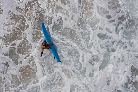 Aerial from a surfer going to surf in the atlantic ocean Standard-Bild - 123552997