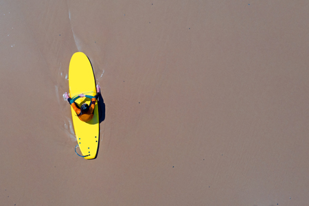 Aerial from a surfer relaxing on her surfboard at the atlantic ocean Standard-Bild - 123553082