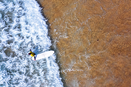 Aerial shot from a surfer going to surf in the ocean Standard-Bild - 123553115