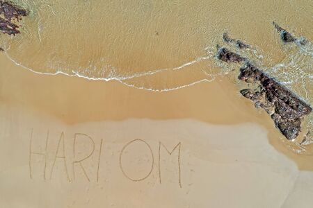 Aerial top shot from ocean waves and handwritten Hari Om at the beach