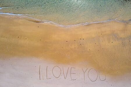 Aerial top shot from ocean waves and handwritten I love you at the beach Imagens