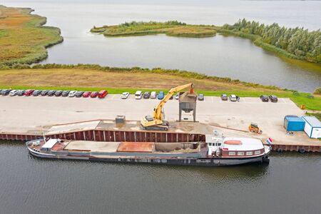 Aerial from freighter unloading sand in the countryside from the Netherlands Stock Photo