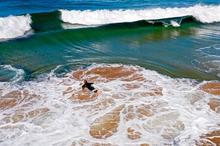 Aerial from a young surfer ready to surf at the atlantic ocean Foto de archivo