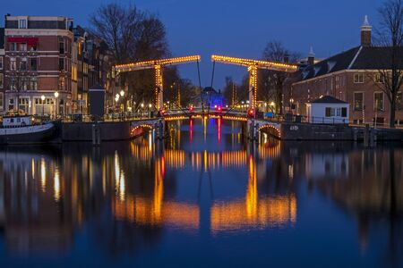 City scenic from Amsterdam at the Amstel in the Netherlands at night