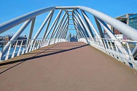 Walk way on modern bridge in the harbor from Amsterdam in the Netherlands